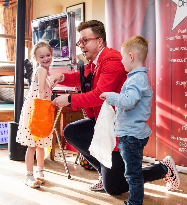Dazzling Darren, A Children's Entertainer In Leeds Shows A Trick to Two Laughing Helpers.